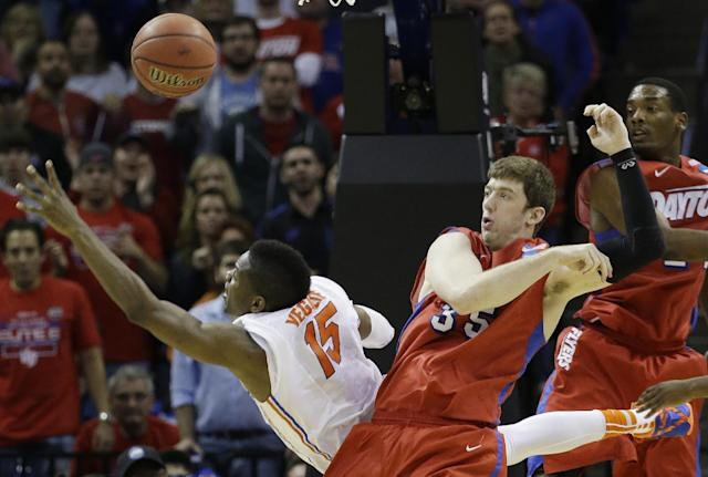 Florida forward Will Yeguete (15) falls to the court as Dayton forward/center Matt Kavanaugh (35) defends during the second half in a regional final game at the NCAA college basketball tournament, Saturday, March 29, 2014, in Memphis, Tenn. (AP Photo/Mark Humphrey)