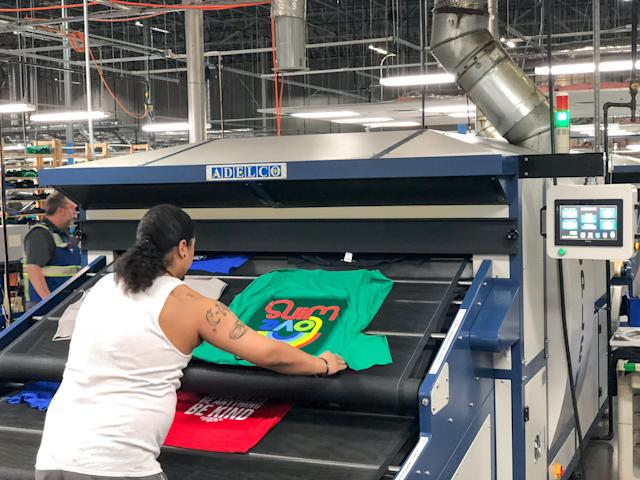 A worker prints T-shirt in an Amazon facility for the Merch by Amazon program. (Credit: Amazon)