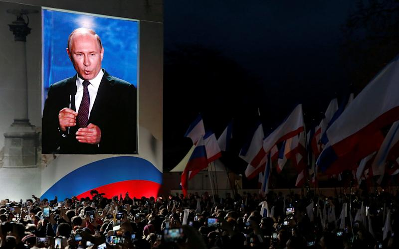 Russian president Vladimir Putin addresses the audience during a rally marking the fourth anniversary of Russia's annexation of Ukraine's Crimea region in the Black Sea port of Sevastopol - REUTERS