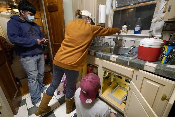 CORRECTS SPELLING OF LAST NAME TO VALERIO, NOT VALERIA - Roberto Valerio Jr., left, and his cousin Hector Valerio, right, look on as homeowner Nora Espinoza test for water coming out of the faucet after a repair was made to a pipe break beneath the sink, Saturday, Feb. 20, 2021, in Dallas. Espinoza's home experienced multiple pipe breaks during freezing temperatures brought by last week's winter weather. (AP Photo/Tony Gutierrez)