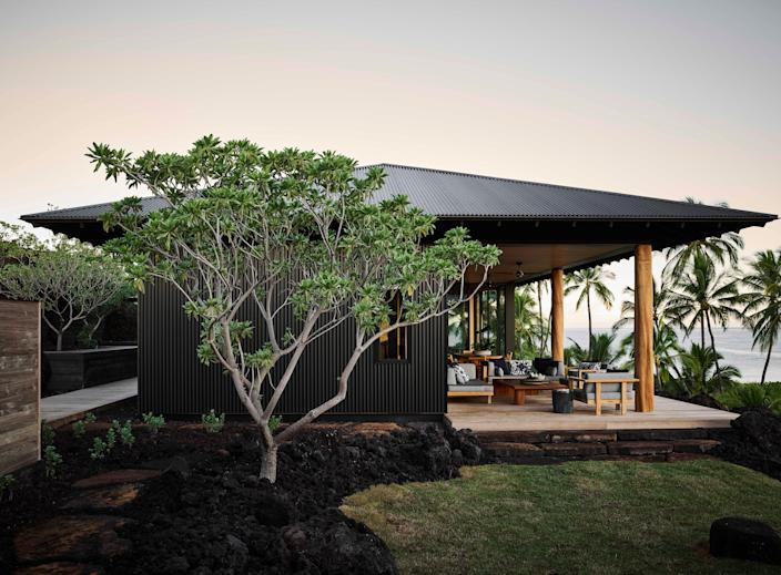 The architecture is inspired by Hawai'i's historic plantations, as are the materials—dark-stained corrugated metal cladding is not only emblematic of the islands' agrarian heritage but also disguises the home in the surrounding lava fields. This corner <em>makai</em> (oceanside) lanai is subject to high winds but incredible coastal views. Furniture from Henry Hall Designs.