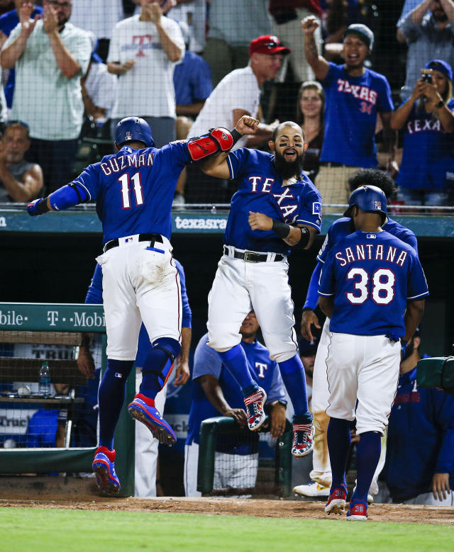 Texas Rangers' Ronald Guzman (11) is congratulated by Rougned Odor, center, after hitting a two-run home run during the eighth inning of a baseball game against the Houston Astros, Friday, July 12, 2019, in Arlington, Texas. (AP Photo/Brandon Wade)