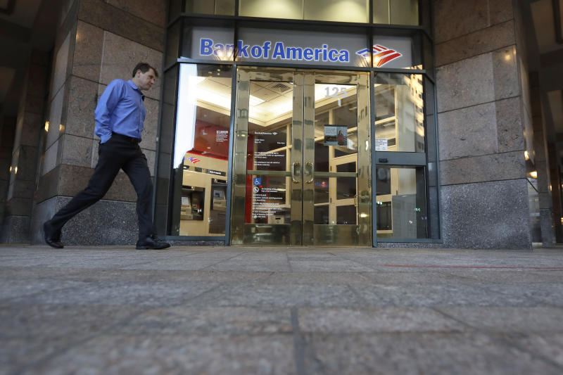 In this Monday, Oct. 14, 2019 photo a passer-by walks past the entrance to a Bank of America ATM, in Boston. Bank of America Corp. reports financial results Wednesday, Oct. 16.(AP Photo/Steven Senne)