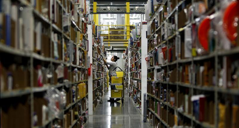 Worker gathers items for delivery from the warehouse floor at Amazon's distribution center in Phoenix