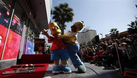 """The characters of Homer (R) and Bart Simpson pose by the star of Matt Groening, creator of """"The Simpsons,"""" before it was unveiled on the Walk of Fame in Hollywood, California February 14, 2012. REUTERS/Mario Anzuoni"""