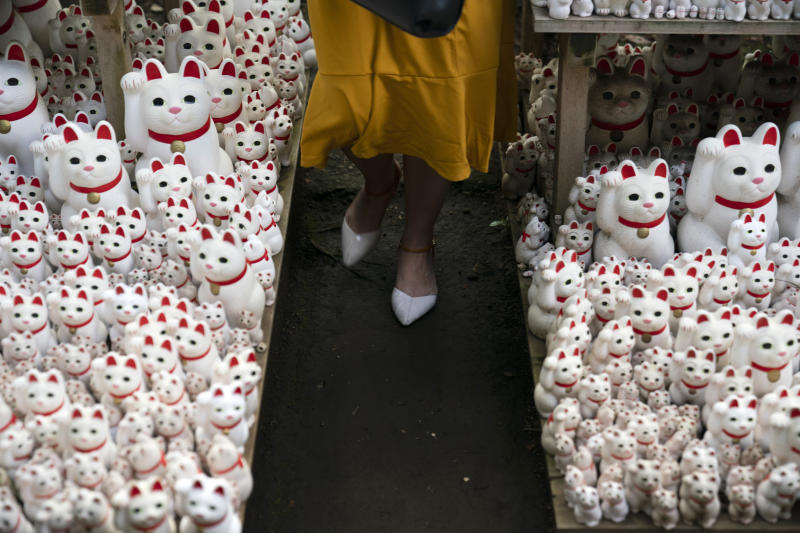 In this June 25, 2019, photo, a tourist walk between beckoning cat figurines after posing for photos with them at Gotokuji Temple in Tokyo. According to a centuries-old legend provided by the temple, Gotokuji, a Buddhist temple located in the quiet neighborhood of Setagaya, is the birthplace of beckoning cats, the famous cat figurines that are widely believed to bring good luck and prosperity to home and businesses. Some visitors come just to snap a few photos, while others make a trip to the temple to pray and make wishes. (AP Photo/Jae C. Hong)