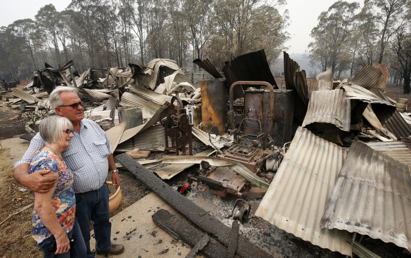 A man and woman stand looking at their burnt down property.