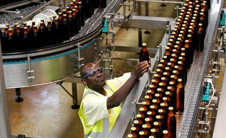 A worker inspects beer bottles on a conveyor belt at the East African Breweries Ruaraka factory in Nairobi