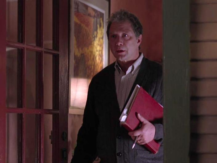 Jeff Perry as Thatcher on Greys Anatomy, standing in a door way holding a folder while wearing a cardigan