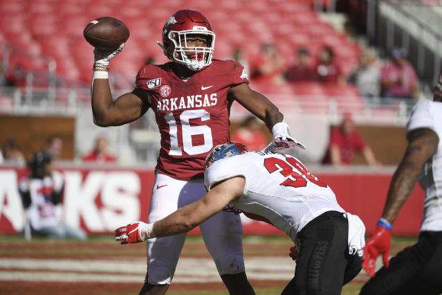 Arkansas receiver Treylon Burks is tackled by Western Kentucky defender Clay Davis as he tries to throw a pass during the second half of an NCAA college football game, Saturday, Nov. 9, 2019 in Fayetteville, Ark. (AP Photo/Michael Woods)
