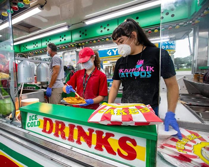 Food vendor employees Delaney Mcgrath, 14, and Fiorella Moreno, 18 prepare a elephant ear dessert during the Miami-Dade County Youth Fair food drive-through in Miami, Florida on Saturday, July 11, 2020.