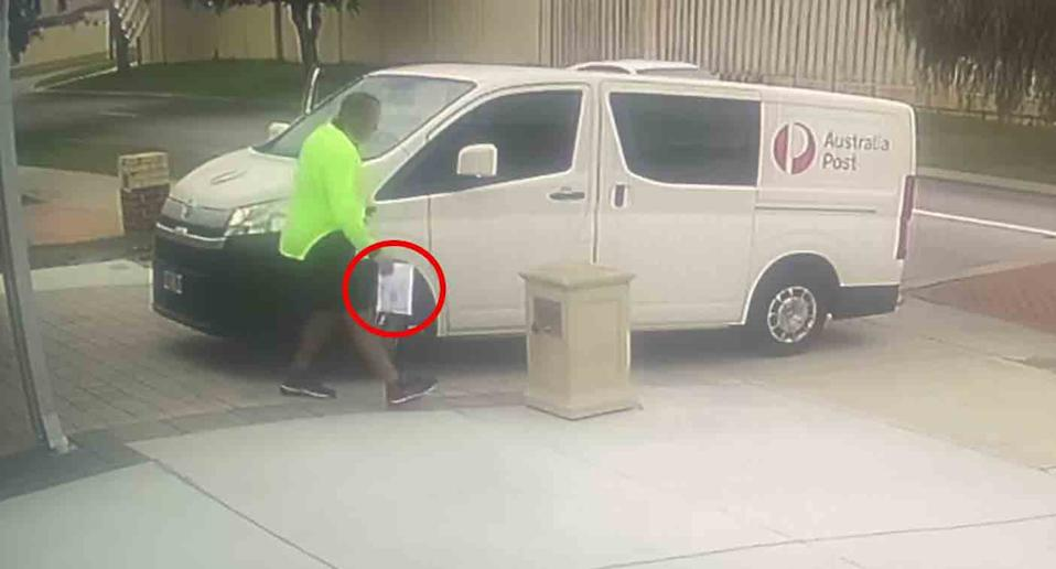 The Australia Post delivery driver goes to place the package behind the resident's mailbox.
