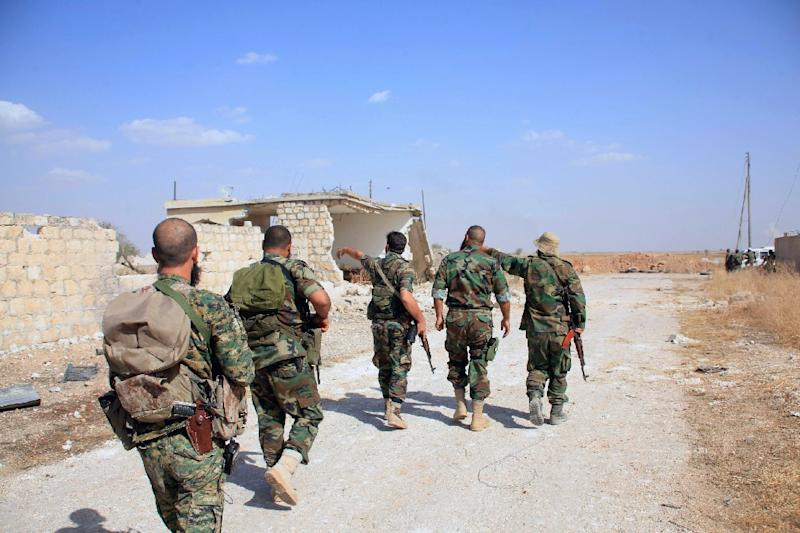 Syrian regime soldiers walk down a road in an area around Kweyris military airport, in the eastern Aleppo province on October 16, 2015
