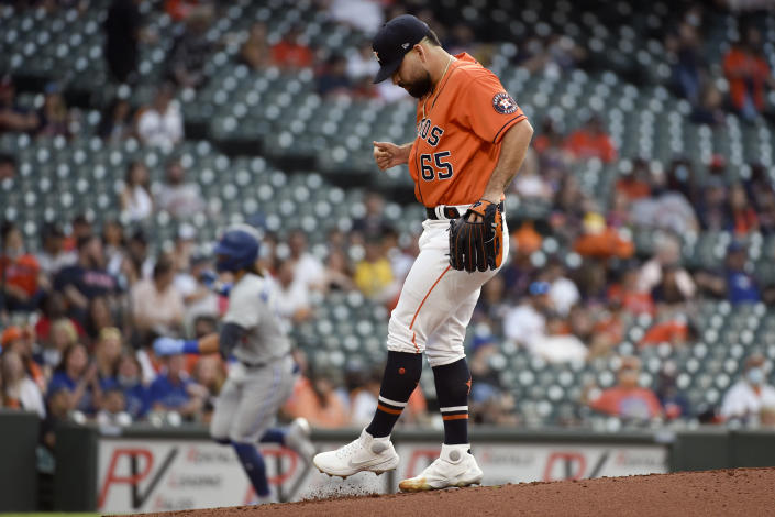 Houston Astros starting pitcher Jose Urquidy (65) kicks the mound as Toronto Blue Jays' Bo Bichette, back left, rounds the bases after hitting a solo home run during the first inning of baseball game, Friday, May 7, 2021, in Houston. (AP Photo/Eric Christian Smith)