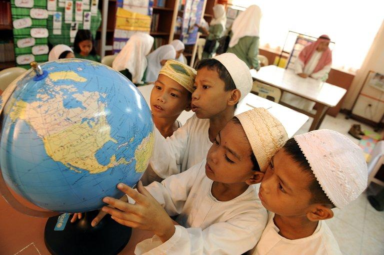 Students look at a globe  in the Baseco government elementary school in Manila on October 9, 2008