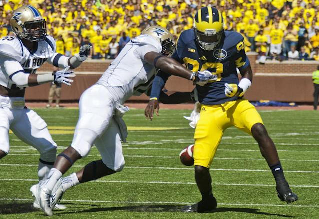 Akron wide receiver Zach D'Orazio, center, strips the ball from Michigan quarterback Devin Gardner (98) causing a fumble in the second quarter of an NCAA college football game, Saturday, Sept. 14, 2013, in Ann Arbor, Mich. (AP Photo/Tony Ding)