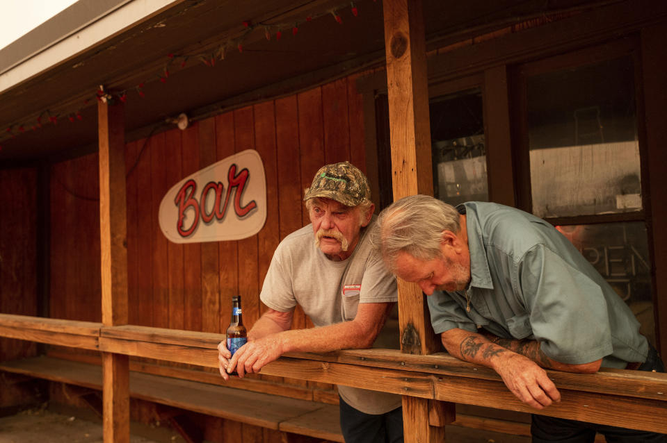 Dave Ferner, left, and Bob Prary watch as multiple homes burn in central Doyle, Calif., as the Sugar Fire, part of the Beckwourth Complex Fire, tears through town on Saturday, July 10, 2021. Ferner said he saved his home using a bulldozer earlier in the day and Prary lost his ranch to a wildfire in November 2020. (AP Photo/Noah Berger)