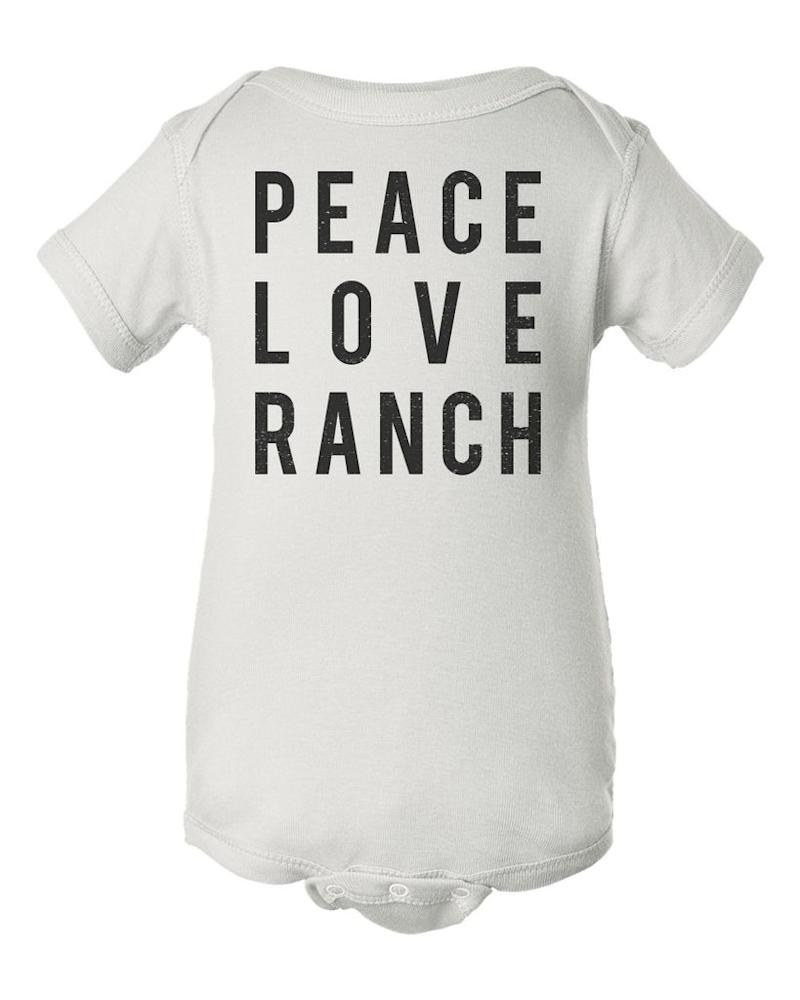"Buy the <a href=""https://www.flavourgallery.com/collections/hidden-valley-ranch/products/hidden-valley-ranch-peace-love-ranch-baby-onesie-1"" target=""_blank"">'Peace, Love, Ranch' baby onesie </a>for $25"