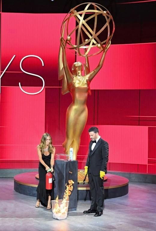 In one early on-stage gag, Emmys host Jimmy Kimmel set an awards envelope on fire to sterilize it, with Jennifer Aniston dousing the flames