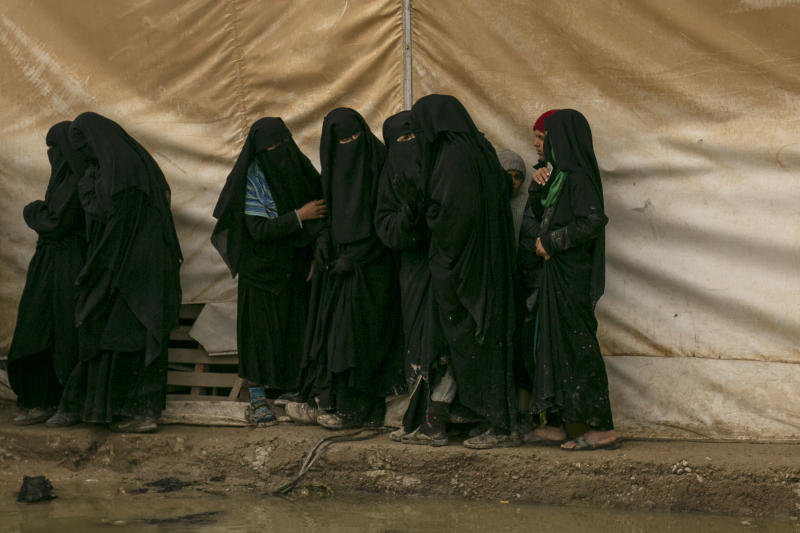 In this March 31, 2019 photo, women line up for aid supplies at Al-Hol camp, home to Islamic State-affiliated families near Hasakeh, Syria. The IS could get a new injection of life if conflict erupts between the Kurds and Turkey in northeast Syria as the U.S. pulls its troops back from the area. The White House has said Turkey will take over responsibility for the thousands of IS fighters captured during the long campaign that defeated the militants in Syria. But it's not clear how that could happen. (AP Photo/Maya Alleruzzo)
