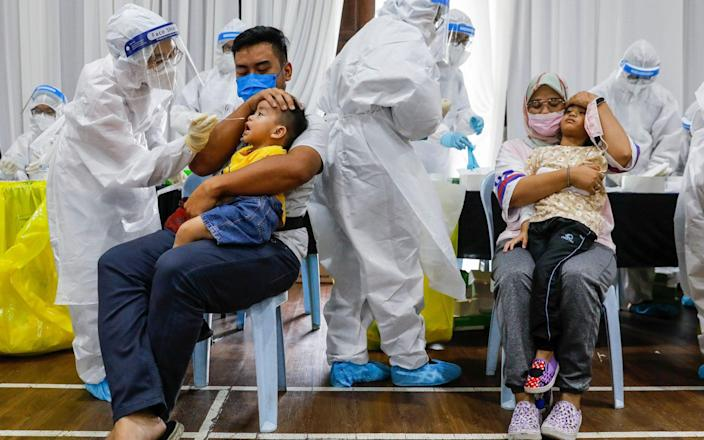 Parents comfort their children as medical personnel collect swab samples for Covid-19 testing in Selangor - FAZRY ISMAIL/EPA-EFE/Shutterstock