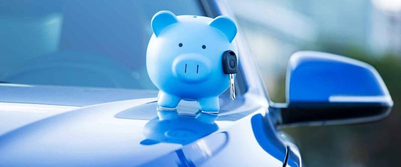 Closeup image new car with piggy bank, illustrating car insurance