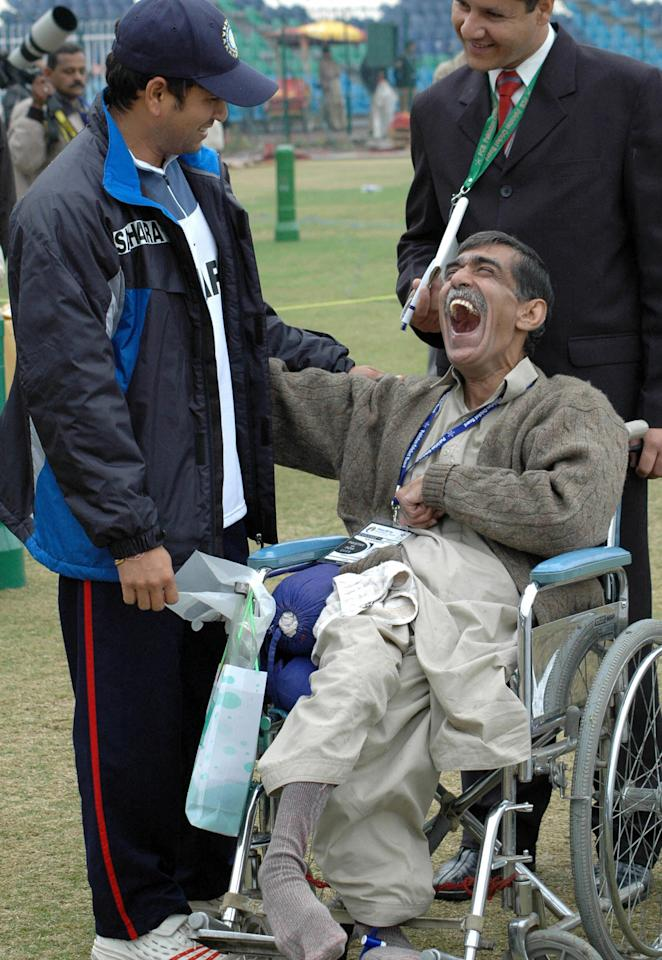 Lahore, PAKISTAN:  Indian cricketer Sachin Tendulkar shares a light moment with a disabled cricket fan at the Gaddafi Cricket Stadium at the close of play on the final day of the first Test match between Pakistan and India, Lahore, 17 January 2006. The match ended in a draw as India reached 410-1 in reply to Pakistan's mammoth first innings total of 679-7 declared before play was called off after just 2.2 overs on the fifth and final day. The second match of the three Test match series will starts at Faisalabad from January 21-25 and the third and final Test will be played in Karachi from January 29-February 2.   AFP PHOTO /Arif ALI  (Photo credit should read Arif Ali/AFP/Getty Images)