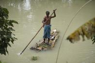 A man uses a banana tree raft to move across a flooded area in a flood effected village in Morigaon district of Assam in India on Friday, 17 July 2020. (Photo by David Talukdar/NurPhoto via Getty Images)