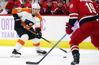 Philadelphia Flyers' Ivan Provorov (9), of Russia, tries to shoot the puck past Carolina Hurricanes' Dougie Hamilton (19) during the first period of an NHL hockey game in Raleigh, N.C., Thursday, Nov. 21, 2019. (AP Photo/Karl B DeBlaker)