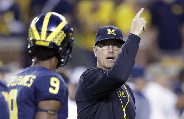 Michigan head coach Jim Harbaugh, right, signals to his team during warmups for an NCAA college football game against Michigan State, Saturday, Oct. 7, 2017, in Ann Arbor, Mich. (AP Photo/Carlos Osorio)