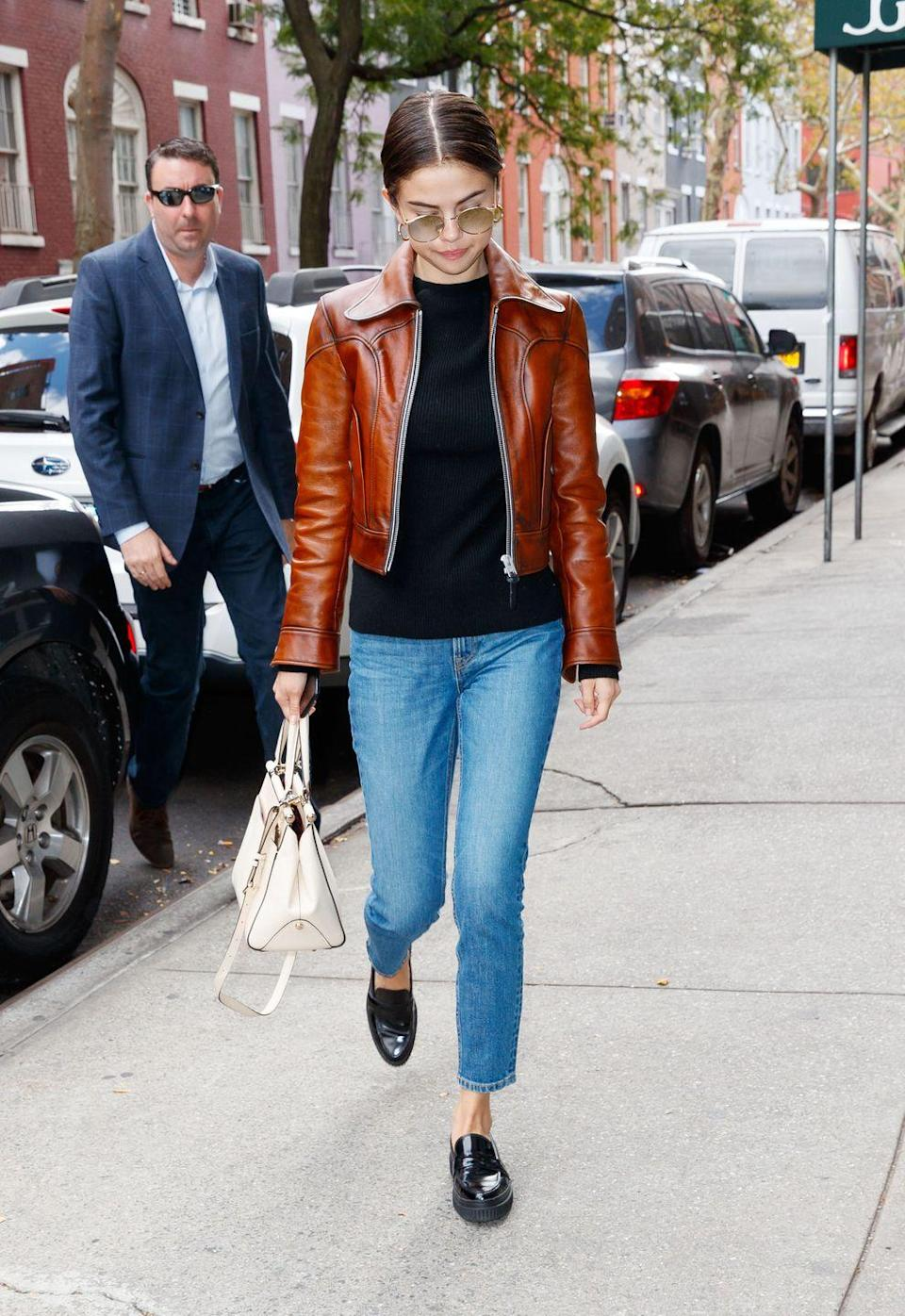 <p>The star wore a Coach brown leather jacket with black pumps and jeans for a day out in the Big Apple, September 2017.</p>