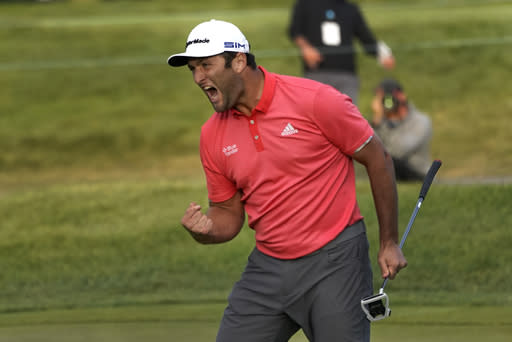 Jon Rahm reacts after making his putt on the first playoff hole during the final round of the BMW Championship golf tournament at the Olympia Fields Country Club in Olympia Fields, Ill., Sunday, Aug. 30, 2020. Rahm wasn't aware Dustin Johnson had forced the playoff because without a gallery there was no cheer. (AP Photo/Charles Rex Arbogast)