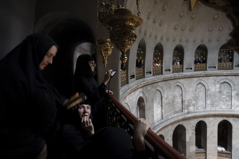 Greek Orthodox nuns wait for the ceremony of the Holy Fire at Church of the Holy Sepulchre, where many Christians believe Jesus was crucified, buried and rose from the dead, in the Old City of Jerusalem, Saturday, May 1, 2021. Thousands of Christians have gathered in Jerusalem for the ancient fire ceremony that celebrates Jesus' resurrection. (AP Photo/Oded Balilty)