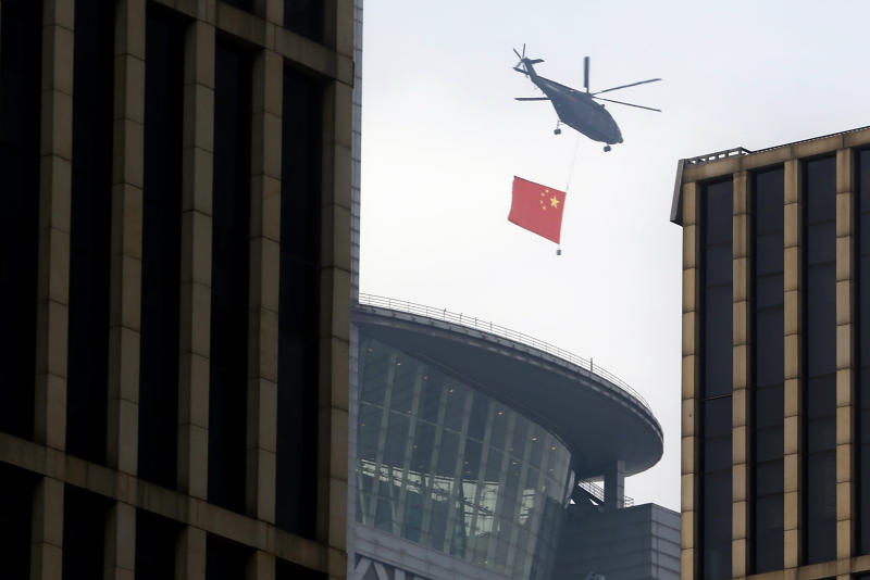 A helicopter carrying the Chinese flag flies above the central business district in Beijing, Sunday, Sept. 15, 2019. Many of the streets in the central part of China's capital were shut down this weekend for a rehearsal for what is expected to be a large military parade on Oct. 1 to commemorate the 70th anniversary of Communist China. (AP Photo/Mark Schiefelbein)