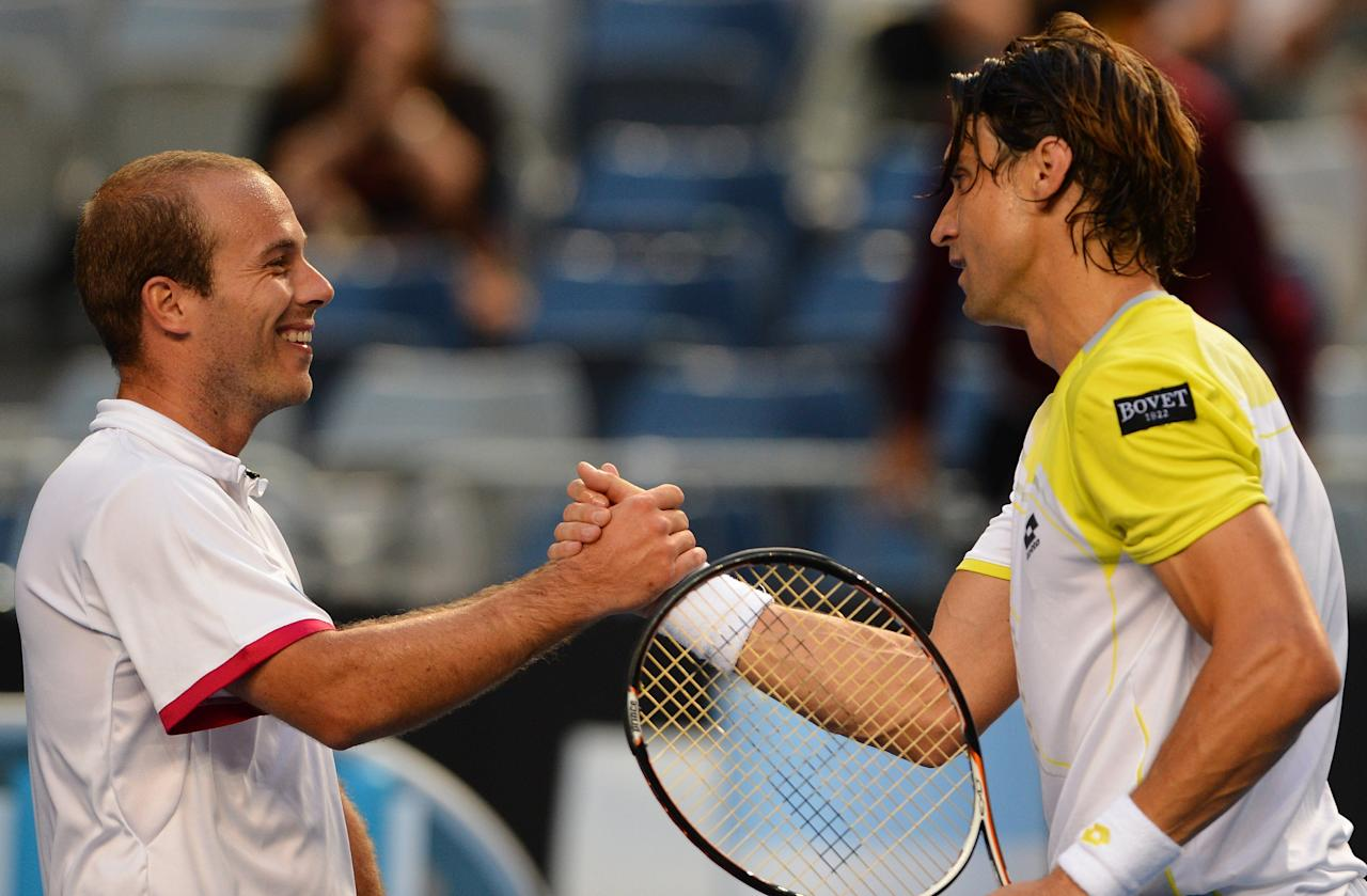 Spain's David Ferrer looks (R) shakes hands after his victory against Belgium's Olivier Rochus (L) on day one of the Australian Open tennis tournament in Melbourne on January 14, 2013.  AFP PHOTO / WILLIAM WEST IMAGE STRICTLY RESTRICTED TO EDITORIAL USE - STRICTLY NO COMMERCIAL USEWILLIAM WEST/AFP/Getty Images