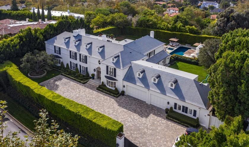 Secluded behind mature hedges, the traditional-style home includes a park-like backyard with a two-bedroom guesthouse and studio.