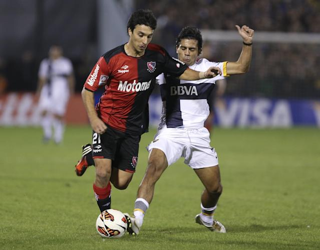 Ignacio Scocco of Argentina's Newell's Old Boys, left, vies for the ball with Walter Erviti of Argentina's Boca Juniors, during a Copa Libertadores soccer match in Rosario, Argentina, Wednesday, May 29, 2013. (AP Photo/Daniel Jayo)
