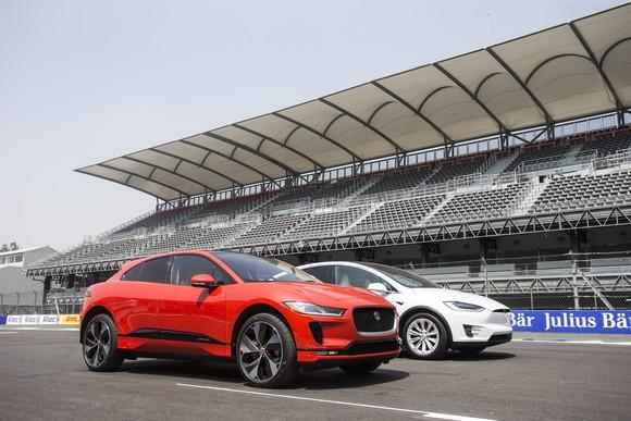 A red Jaguar I-Pace, an electric crossover SUV, is shown on a racetrack's starting line next to a while Tesla Model X SUV.