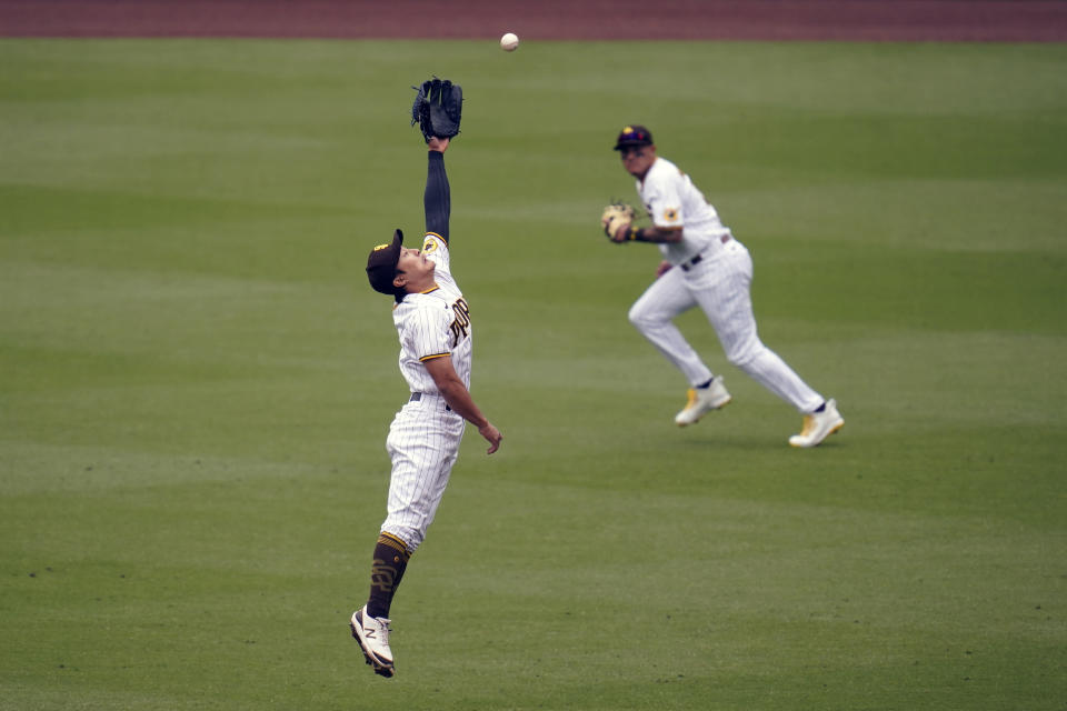 San Diego Padres second baseman Ha-Seong Kim, left, can't reach a hit for a single by Milwaukee Omar Narvaez as center fielder Trent Grisham, right, passes during the fourth inning of a baseball game Wednesday, April 21, 2021, in San Diego. (AP Photo/Gregory Bull)