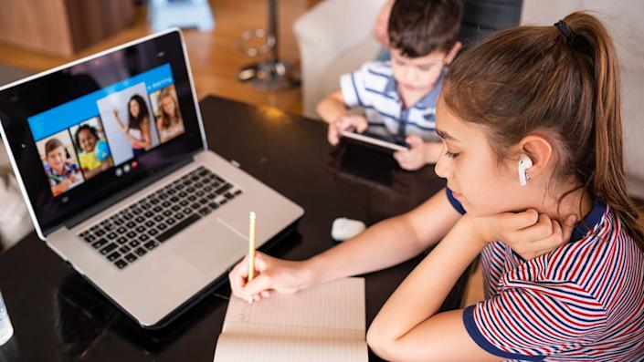 Teenage girl studying with video online lesson at home with her family amid widespread distance learning.