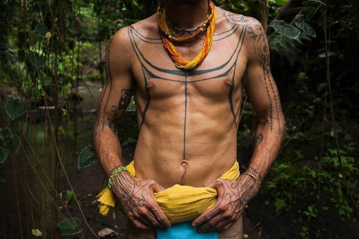 Australian filmmaker and tattoo artist Rob Henry, sporting body tattoo designs from the Mentawai tribe origin, walks in the jungle where a traditional tattoo festival is being held in the village of Maguwoharjo in Yogyakarta (AFP Photo/Suryo Wibowo)