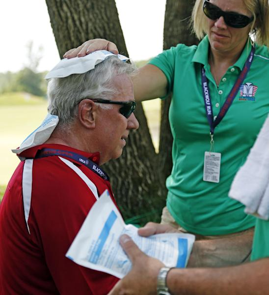 A marshal is treated for heat exhaustion on the 18th green during the first round of the U.S. Women's Open golf tournament, Thursday, July 5, 2012, in Kohler, Wis. Oppressive heat is slamming the middle of the country with record temperatures that aren't going away after the sun goes down. (AP Photo/Jeffrey Phelps)