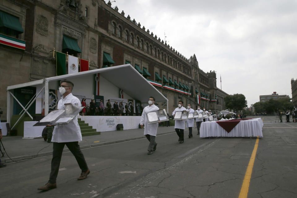 Medical workers who tend to COVID-19 patients pick up their medals, awarded to them by the government in recognition of their efforts in the pandemic, during the annual Independence Day military parade in Mexico City's main square of the capital, the Zócalo, Wednesday, Sept. 16, 2020. Mexico celebrates the anniversary of its independence uprising of 1810. ( AP Photo/Marco Ugarte)