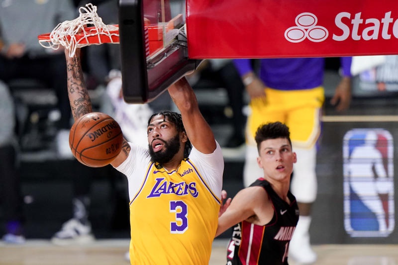 Los Angeles Lakers forward Anthony Davis dunks as Miami Heat guard Tyler Herro looks on during the first half in Game 4 of basketball's NBA Finals Tuesday, Oct. 6, 2020, in Lake Buena Vista, Fla. (AP Photo/Mark J. Terrill)