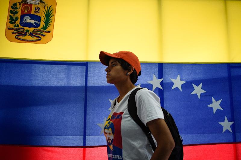 A Juan Guaido supporter listens as the Venezuelan opposition leader speaks to reporters in Caracas on February 18, 2019 (AFP Photo/Federico PARRA)