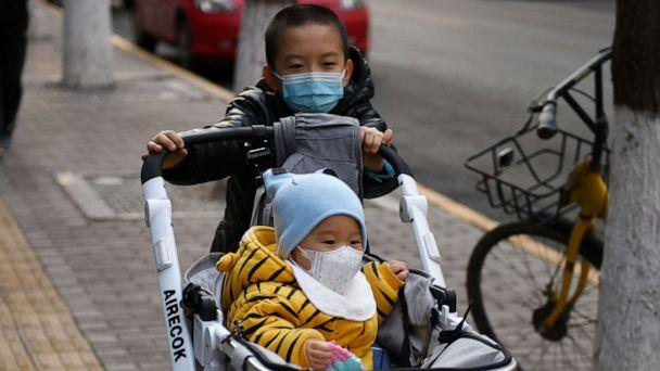 PHOTO: A boy wears a mask as a preventive measure against the COVID-19 coronavirus as as he pushes another child in a pram in Beijing, March 9, 2020. (Greg Baker/AFP via Getty Images)
