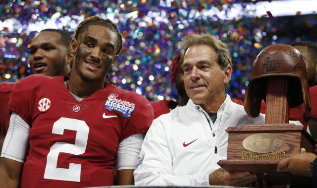 Alabama quarterback Jalen Hurts and Alabama head coach Nick Saban stand with the Leather Helmet trophy after their win over Florida State. (AP)