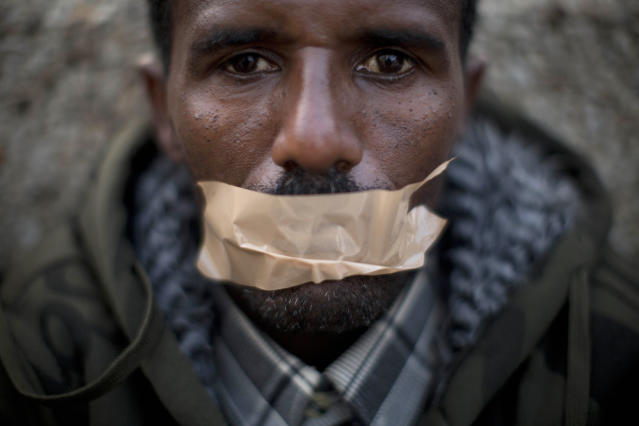 <p>An African migrant covers his mouth with tape during a protest in front of the U.S. Embassy, demanding asylum and work rights from the Israeli government in Tel Aviv, Israel, Jan. 22, 2014. (Photo: Oded Balilty/AP) </p>