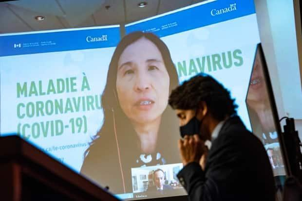 Prime Minister Justin Trudeau puts on a mask as he listens to Chief Public Health Officer of Canada Dr. Theresa Tam speak via video conference during a news conference on the COVID-19 pandemic in Ottawa on March 12, 2021. (Justin Tang/Canadian Press - image credit)