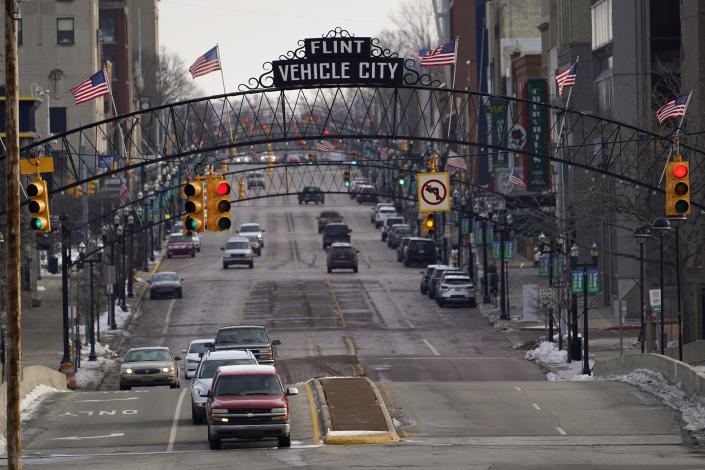 Vehicles drive through downtown Flint, Mich., Wednesday, Jan. 13, 2021. Some Flint residents impacted by months of lead-tainted water are looking past expected charges against former Gov. Rick Snyder and others in his administration to healing physical and emotional damages left by the crisis. (AP Photo/Paul Sancya)